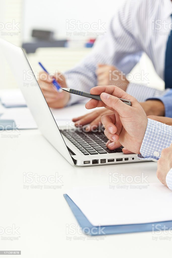 Discussing project Three businessman discussing project on laptop. Close-up on male hands. Adult Stock Photo