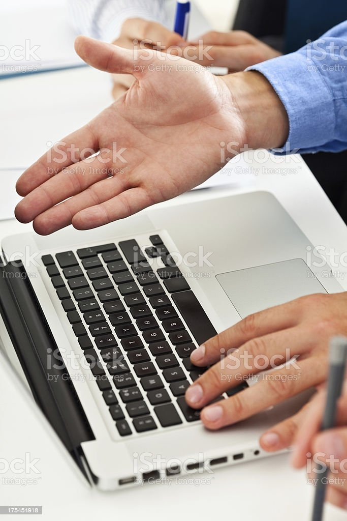 Discussing project Close-up on the businessman's hand showing business project on the laptop.  Adult Stock Photo