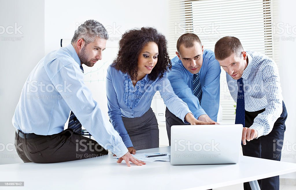 Discussing project Four business people discussing project on laptop in meeting room. 25-29 Years Stock Photo