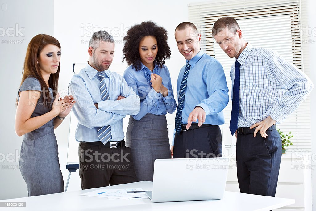 Discussing project Five business people discussing project on laptop in meeting room. 25-29 Years Stock Photo