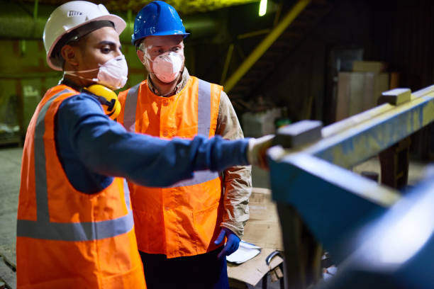 Discussing Results of Joint Work with Colleague Handsome mixed race technician wearing reflective vest pointing at something while discussing results of joint work with his colleague, interior of spacious production department on background manufacturing occupation stock pictures, royalty-free photos & images