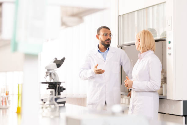 Discussing scientific project in laboratory stock photo