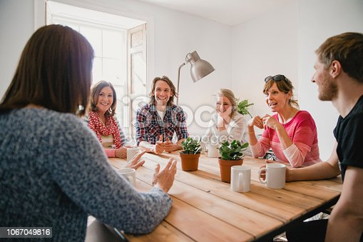 Group of employees at a small coffee shop sitting around a table having a meeting.