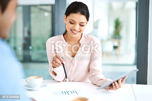Shot of a young businesswoman using a digital tablet during a meeting with her colleague in a modern office