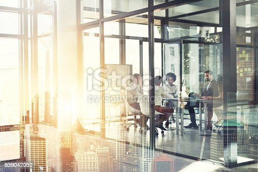 Multiple exposure shot of a businesspeople having a meeting superimposed over a cityscape