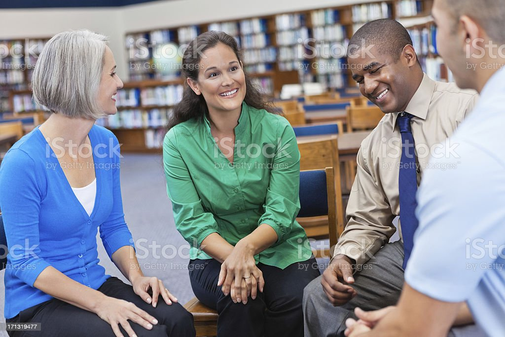 Discussion group laughing together in a library royalty-free stock photo