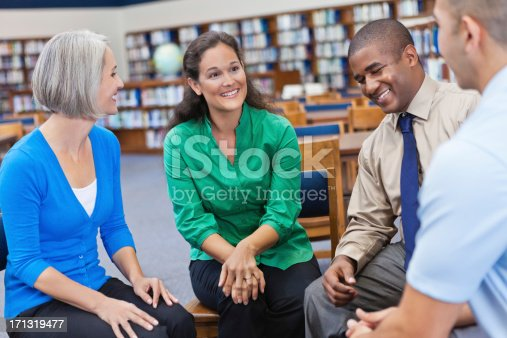 istock Discussion group laughing together in a library 171319477