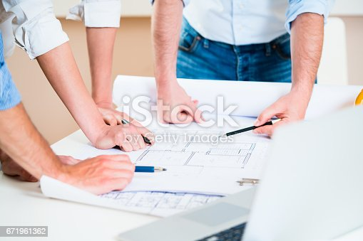 istock Discussion of construction plans in architects office 671961362