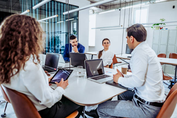 Discussion of important matters. Young business people work in a spacious beautiful office together. Communication and break during work. stock photo