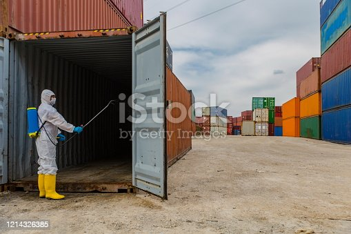 Man wearing protective biological suit and gas-mask due to mers coronavirus global pandemic warning and danger.Medic sphysician scientist make disinfection and ventilation at Containers box from Cargo freight ship