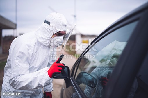 disease control service staff with full protective suit standing in front of geographic border and sign attention with hand on car driver in Europe travelling.