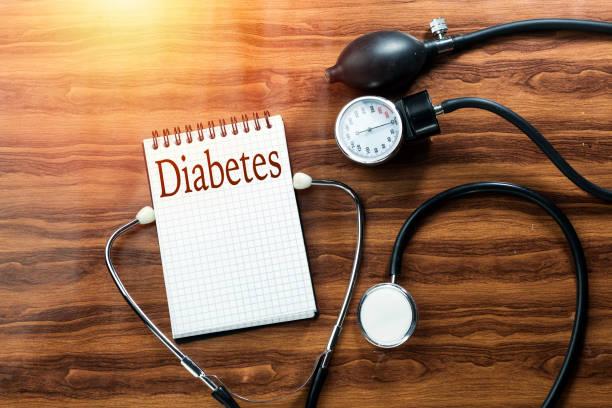 질병 당뇨병 개념 텍스트 흰색 노트북에 검은 청진 기, 혈압 계 나무 테이블에 쓰기 - diabetes 뉴스 사진 이미지