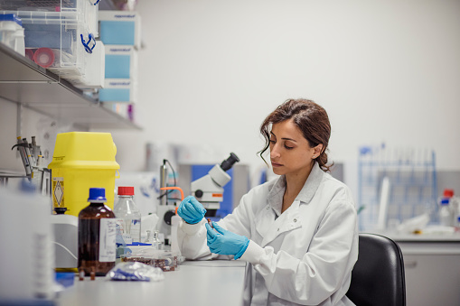 Patient personal health care taken by a specialist biochemist in a London research facility. One women in the lab