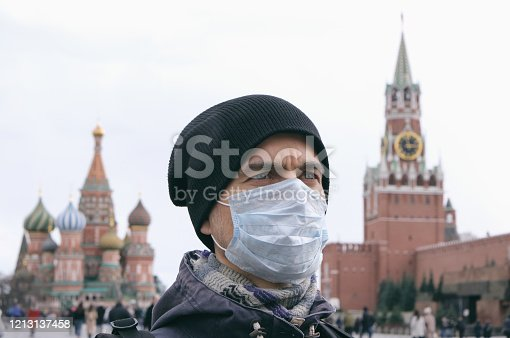 Disease outbreak, coronavirus covid-19 pandemic, air pollution in Moscow, Russia. Portrait of adult man with medical protective mask on face with Kremlin and Red square on background.