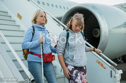 A close-up shot of two mature women disembarking the airplane at an airport, one woman is visually impaired and can be seen holding a cane, they are wearing casual clothing.