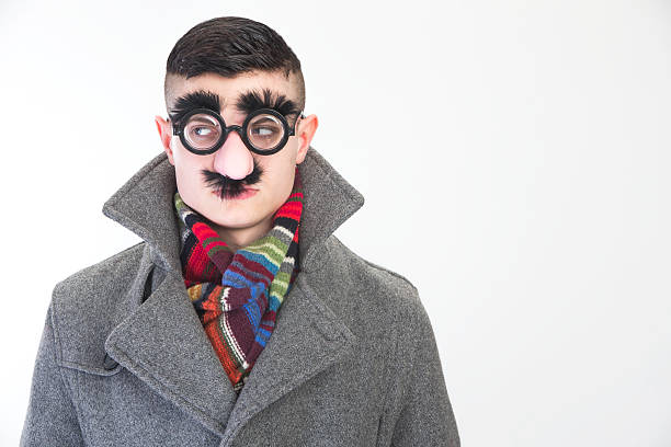 Disguise Young man wearing a silly mask to disguise his face camouflage stock pictures, royalty-free photos & images