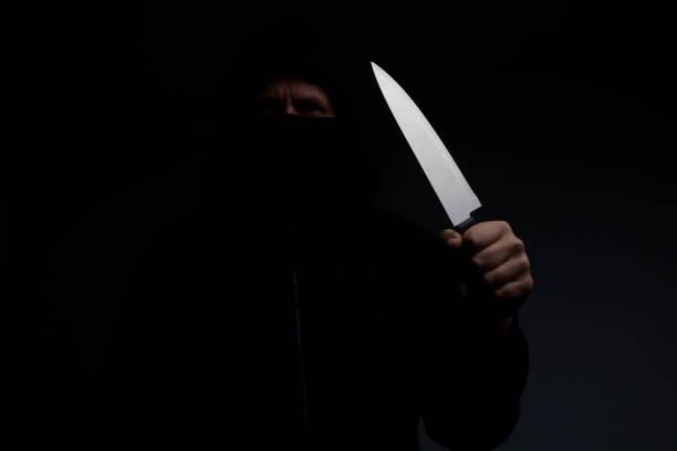 Homem disfarçado, segurando a faca de cozinha com lâmina longa brilhante no quarto em casa no meio da noite - foto de acervo