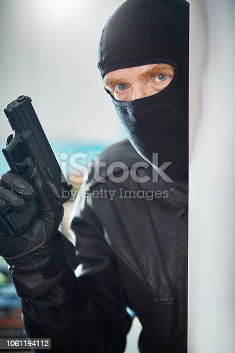 A man in black wearing a balaclava covering his face and carrying a gun peers round a wall in a house. An intruder or a home owner defending his family and property?