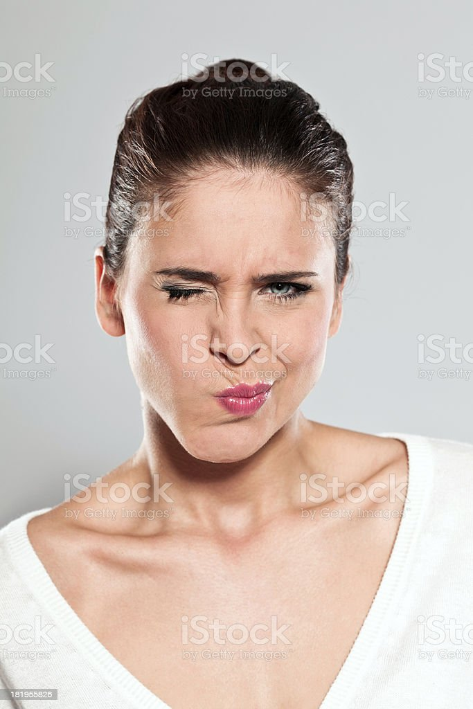 Disgust Portrait of disgusted young woman making a face. Studio shot, grey background. 20-24 Years Stock Photo