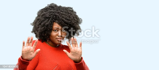 Beautiful african woman disgusted and angry, keeping hands in stop gesture, as a defense, shouting, blue background