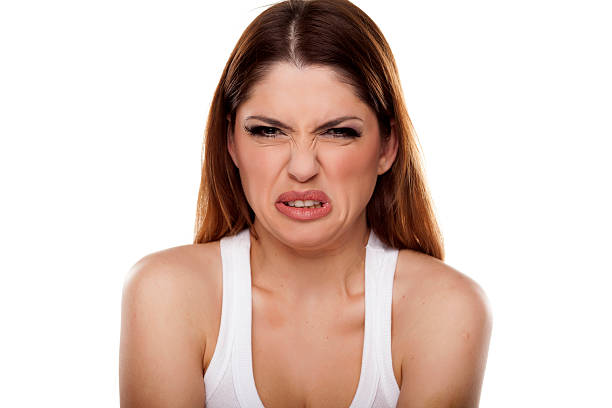 Disgusted and frowning young woman on white background stock photo