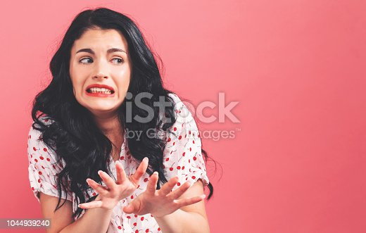 istock Disgusted face expression with young woman 1044939240