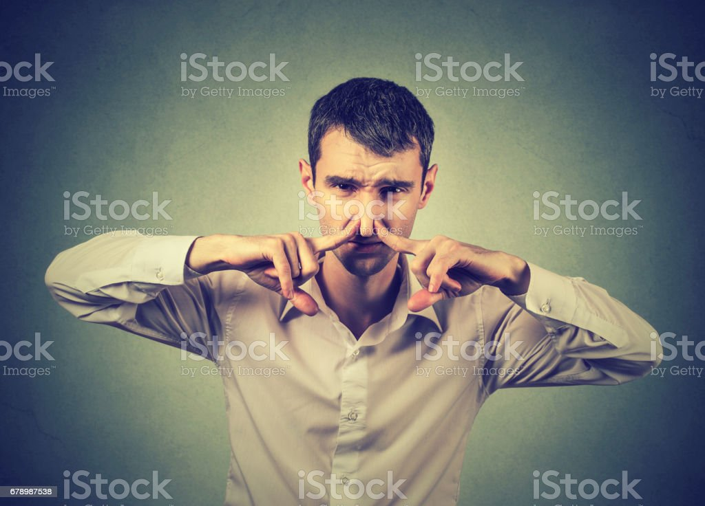 Disgusted man pinches nose with fingers something stinks bad smell royalty-free stock photo