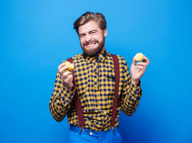 hombre disgustado amargo sabor limón - ácido fotografías e imágenes de stock