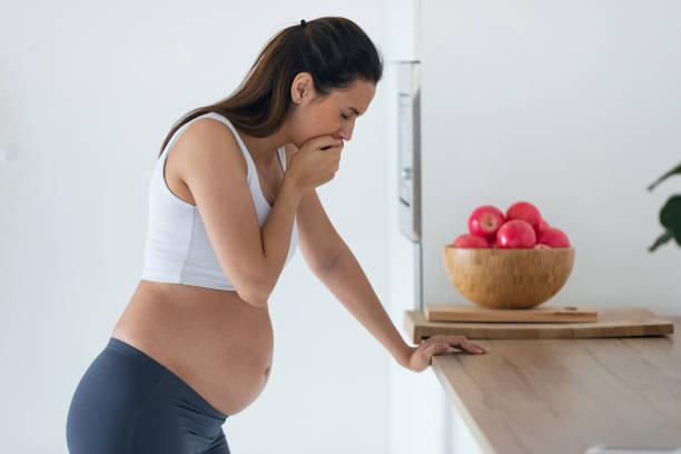 Ekelhafte schwangere junge Frau, die morgens zu Hause an Übelkeit leidet. – Foto