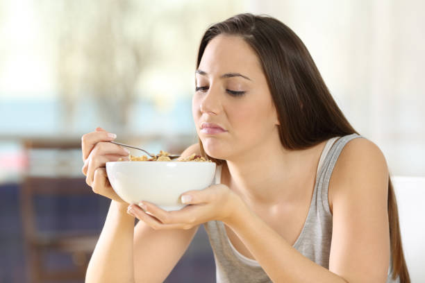 angewidert frau essen getreide mit schlechtem geschmack - zuckerfreie lebensmittel stock-fotos und bilder