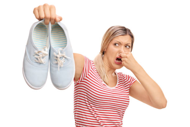 Disgusted woman holding stinky shoes stock photo