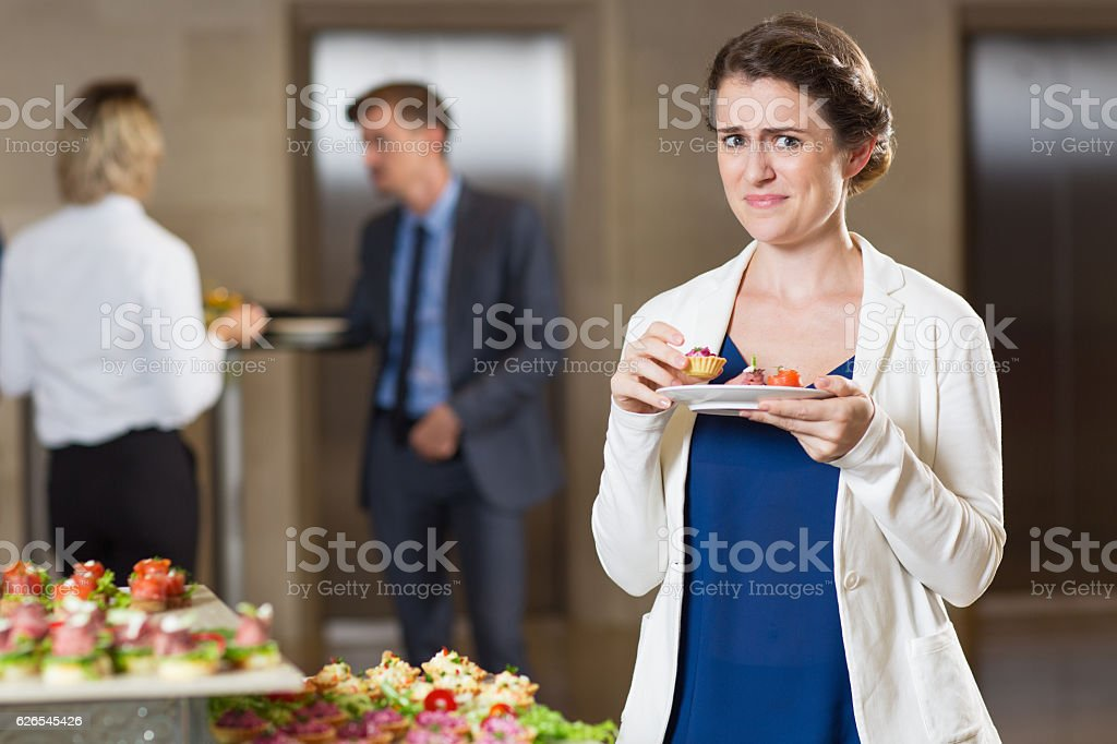 Disgusted Woman Tasting Snacks at Buffet Reception stock photo