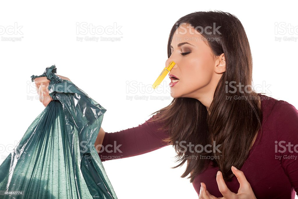 Disgusted young woman holding garbage bag and pinching her nose stock photo