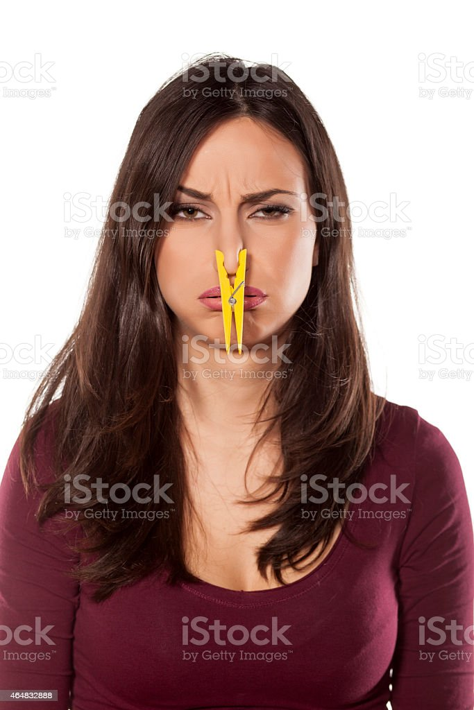 Disgusted young woman pinching her nose with a clothespin stock photo