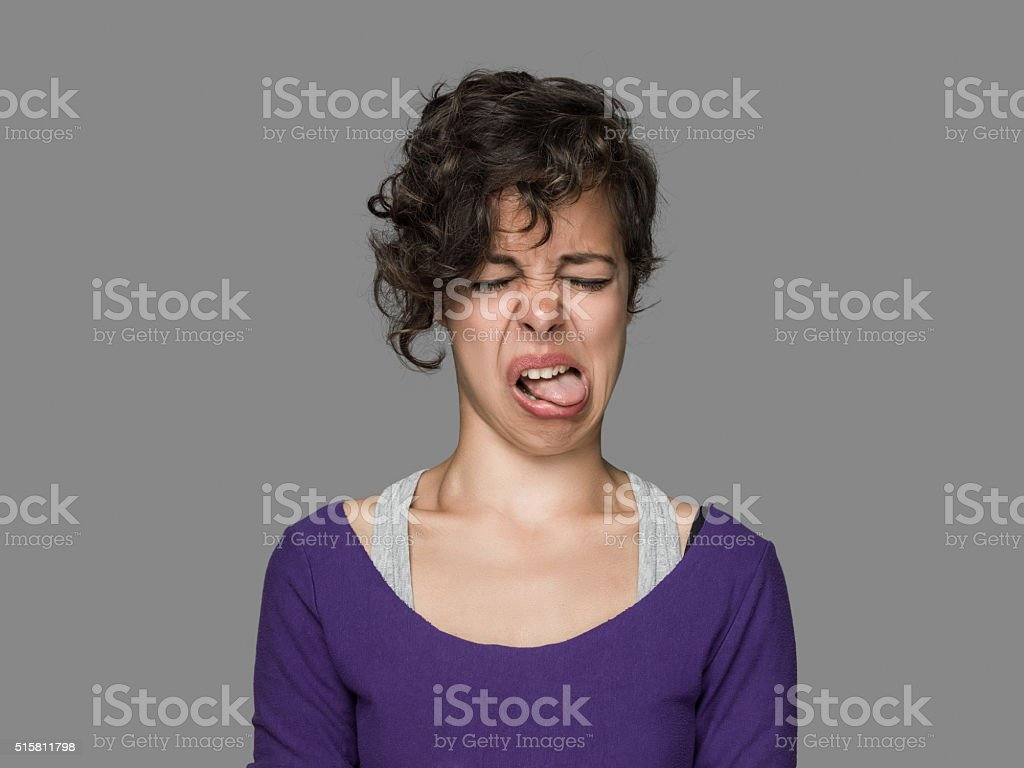 Disgusted Young Woman Sticking Out Tongue stock photo