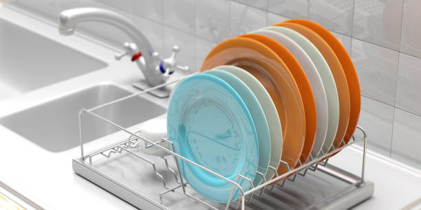 Dish drying rack with colorful plates on a white kitchen counter. 3d illustration Dish drying rack with colorful clean plates on a white kitchen sink counter. 3d illustration crockery stock pictures, royalty-free photos & images