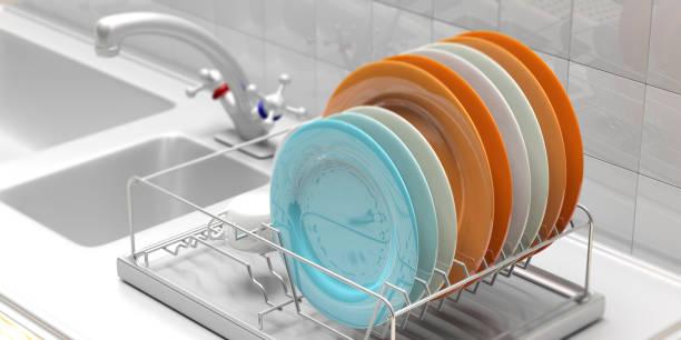 dish drying rack with colorful plates on a white kitchen counter. 3d illustration - naczynia stołowe zdjęcia i obrazy z banku zdjęć