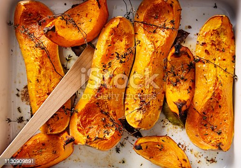 Dish of freshly roasted Butternut squashes cooked until they are soft, with thyme, bay leaves and olive oil. Colour, horizontal with some copy space.