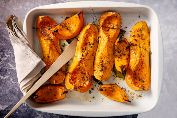 Dish of baked Butternut squashes ready to eat. Dish of freshly roasted Butternut squashes cooked until they are soft, with thyme, bay leaves and olive oil. Colour, horizontal with some copy space. squash vegetable stock pictures, royalty-free photos & images