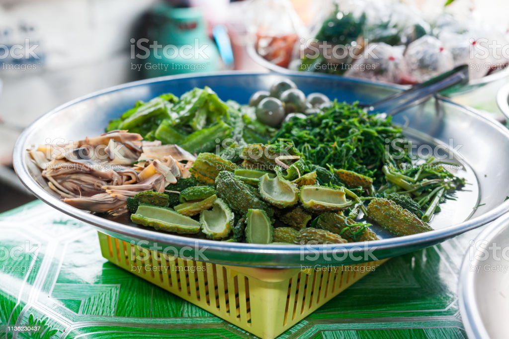 Dish of cooked vegetables ready for sale in a boat at Damnoen Saduak Floating Market. Thailand stock photo