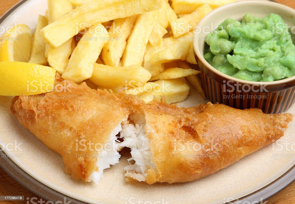 A dish of fish and chips with mushy peas stock photo