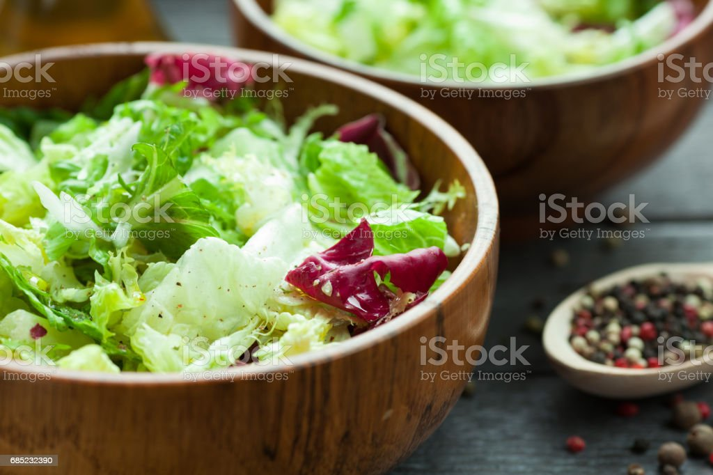 A dish of fresh salad frisse, Romano and radiccio with olive oil, salt and freshly ground percec in a wooden bowl foto de stock royalty-free