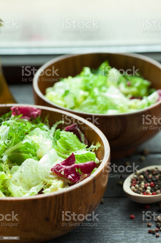 A dish of fresh salad frisse, Romano and radiccio with olive oil, salt and freshly ground percec in a wooden bowl stock photo