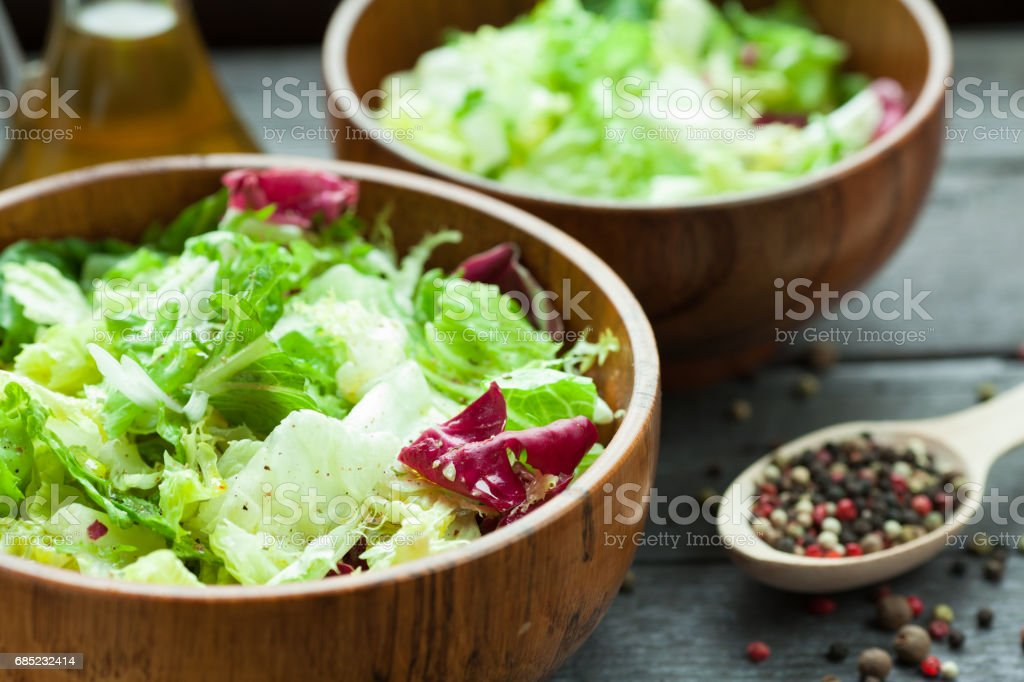A dish of fresh salad frisse, Romano and radiccio with olive oil, salt and freshly ground percec in a wooden bowl royalty-free stock photo
