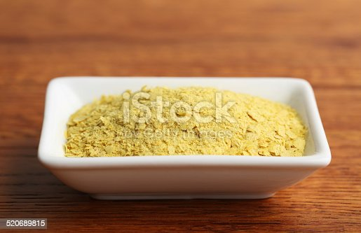 Small dish of nutritional yeast on a wooden background.  Shot in studio with a Canon 5D Mark III.