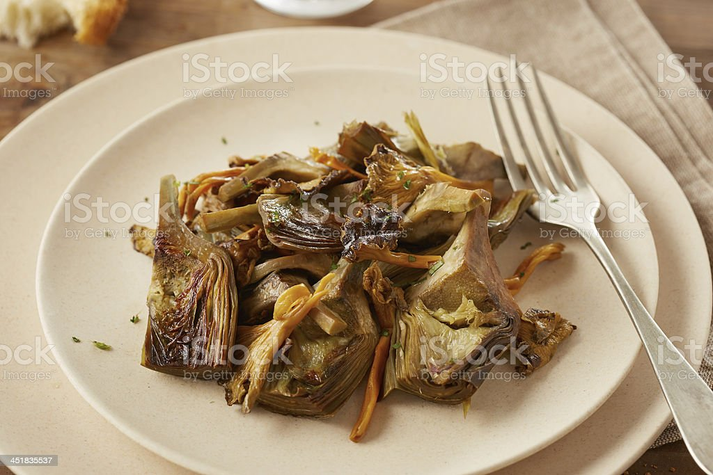 Dish of sauteed artichokes and yellow foot mushrooms stock photo