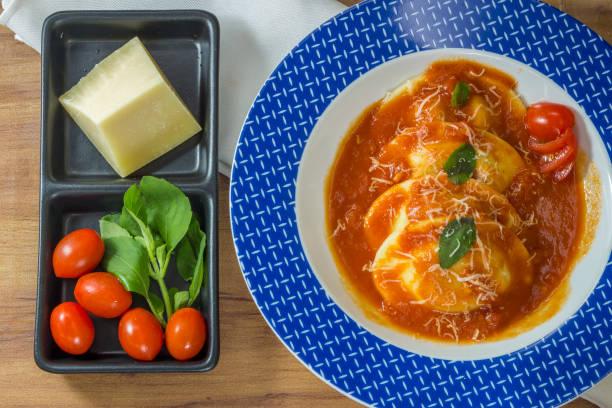 schüssel mit sorrentinos - nudeln gefüllt - mit sauce und mit einigen basilikumblättern dekoriert. - pasta deli stock-fotos und bilder