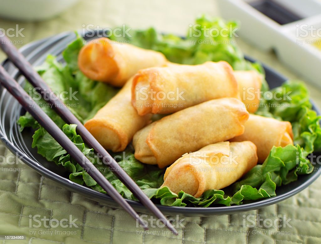 Dish of spring rolls on lettuce with chopsticks stock photo