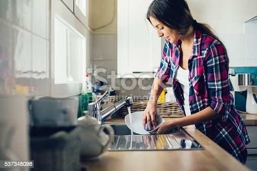 Beautiful young woman washing dishes. Shot made during Istockalypse Paris 2016 event.