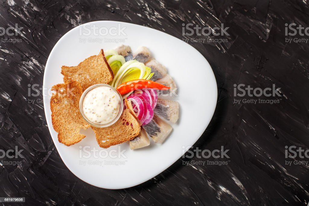 Dish with herring and bread chips and chilli. Top view. The concept of food, restaurant, banquet. stock photo